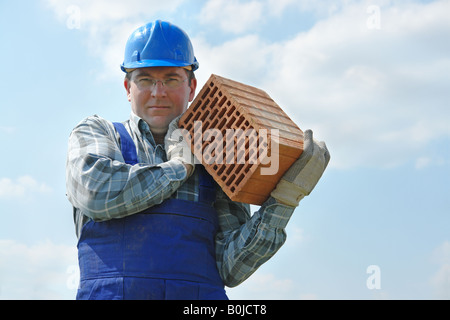 Construction worker in blue jumpsuit and helmet carrying hollow brick - Stock Photo