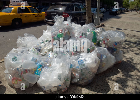 Plastic glass and metal containers packed in clear plastic bags await pick up curbside - Stock Photo