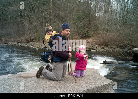 A Man hiking with his two small children near a river in the forest - Stock Photo