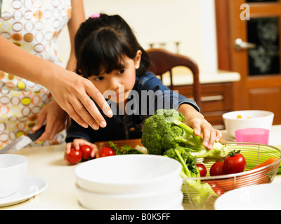 Daughter helping mother cooking - Stock Photo