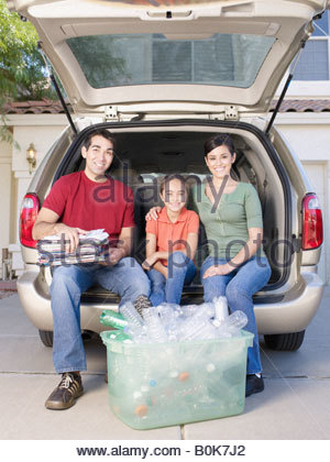 Man with woman and young girl sitting in back of van with bin of recyclable materials smiling - Stock Photo