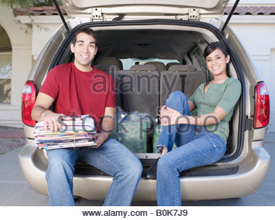 Man and woman sitting in back of van with bin of recyclable materials smiling - Stock Photo