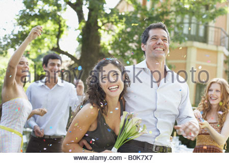 Couple outdoors at party carrying flowers and having confetti thrown at them - Stock Photo