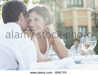 Couple at outdoor party whispering and smiling - Stock Photo