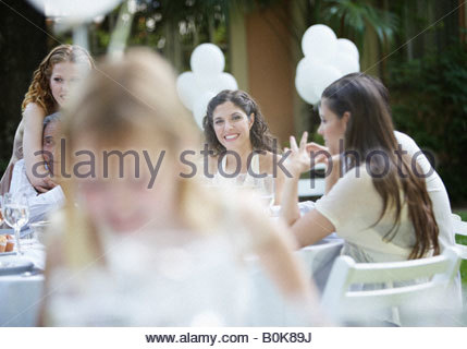 group of people at an outdoor party talking and smiling where a young girl is blurred in foreground - Stock Photo