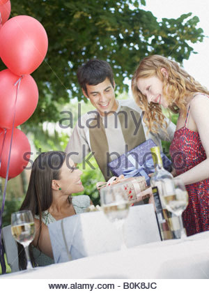 Partygoers at outdoor party giving gifts to woman and smiling - Stock Photo