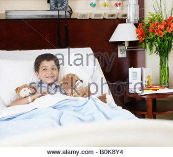 Young boy lying in hospital bed with teddy bears - Stock Photo