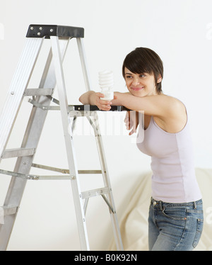 Young Woman Leaning on Stepladder and Holding Light bulb - Stock Photo