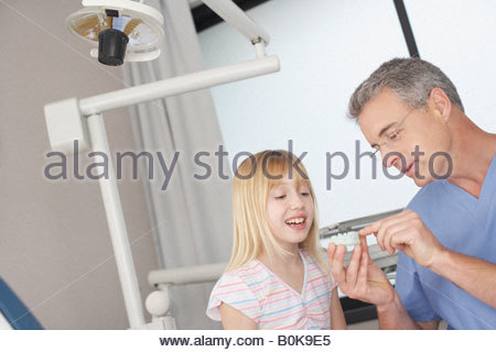 Dentist in examination room showing smiling young patient mold of teeth - Stock Photo