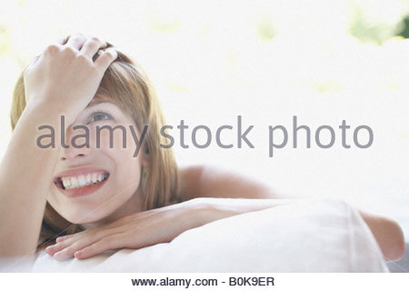 Woman outdoors lying on patio lounger laughing - Stock Photo