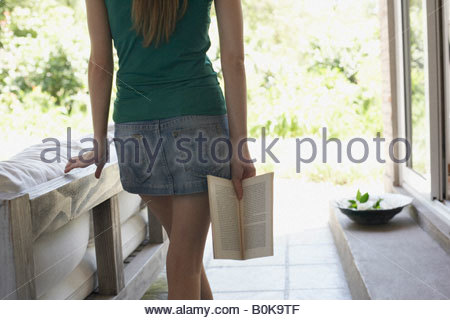 Woman standing outdoors on patio with a book - Stock Photo