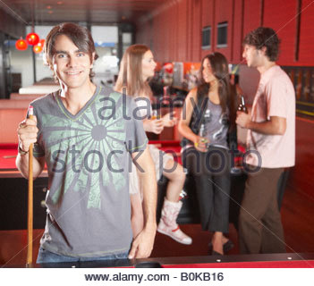 Man holding pool cue by pool table and smiling - Stock Photo