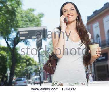 Woman outdoors using cellular phone and smiling - Stock Photo
