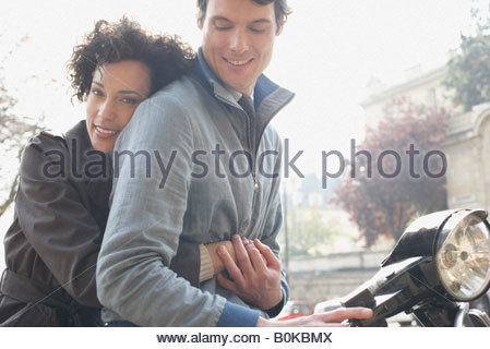 Couple outdoors on an electric scooter smiling - Stock Photo