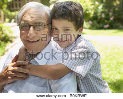 Senior man sitting outdoors with young boy being affectionate toward him and smiling - Stock Photo
