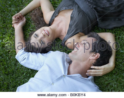 Couple outdoors lying on grass together holding hands and smiling - Stock Photo