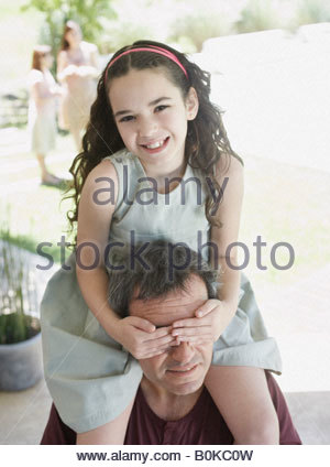 Man outdoors with young girl on shoulders covering his eyes and smiling - Stock Photo