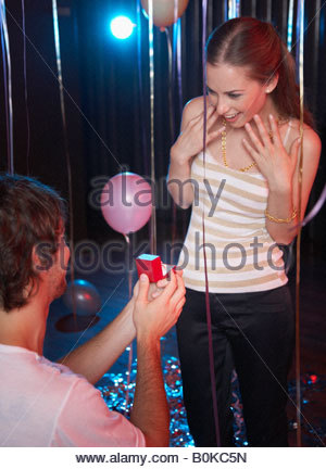 Man proposing to smiling woman in nightclub - Stock Photo