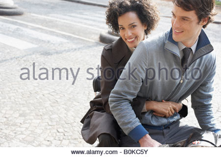Couple outdoors on electric scooter smiling - Stock Photo