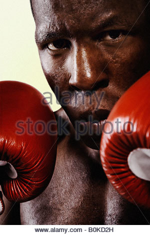 Boxer wearing gloves looking intimidating - Stock Photo