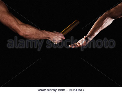 Two relay runners handing off a baton - Stock Photo