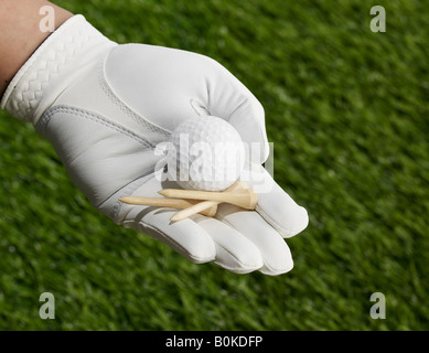 Golf Tees and Ball in Hand - Stock Photo