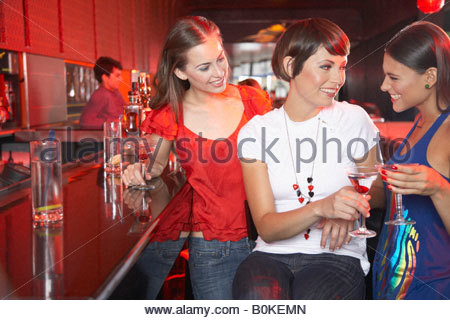Three women in nightclub at bar with beverages toasting and smiling - Stock Photo