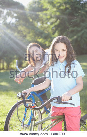Young girl and senior woman outdoors with bicycles smiling - Stock Photo
