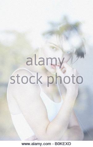 Shot of woman through windowpane thinking - Stock Photo