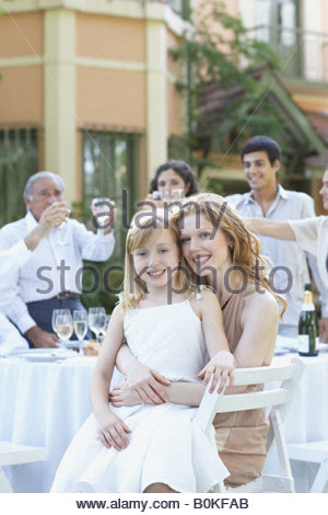 Woman and young girl at outdoor party embracing and smiling - Stock Photo