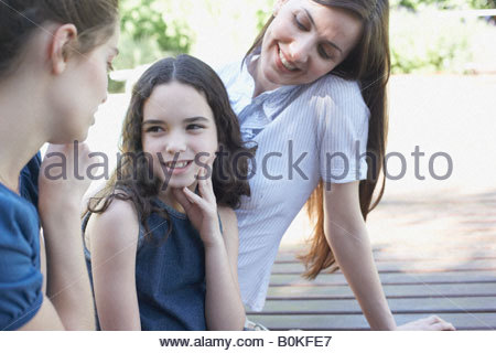 Two women sitting on deck playing with young girl and smiling - Stock Photo