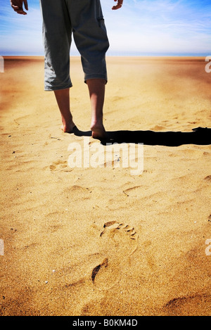 man walking bare foot alone on sand with clear footprint left in soft sand - Stock Photo