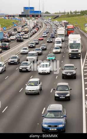 Four lane traffic cars and trucks motoring in congestion on M25 motorway London United Kingdom - Stock Photo