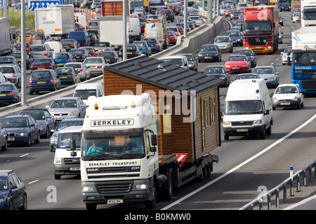 Prefabricated house being transported by road on truck in congested traffic on M25 motorway London United Kingdom - Stock Photo