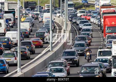 Cars and a motorcyclist in traffic congestion on M25 motorway near London United Kingdom - Stock Photo