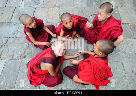 Young Bhutanese Buddhist monks resting from studies at the Wangdue Phodrang Monastry Dzong  in central Bhutan. - Stock Photo