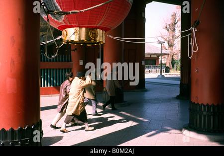 Feb 16, 2004 - Elderly worshippers passing the Hozomon (Treasure House) gate in Tokyo's historic district Asakusa. - Stock Photo