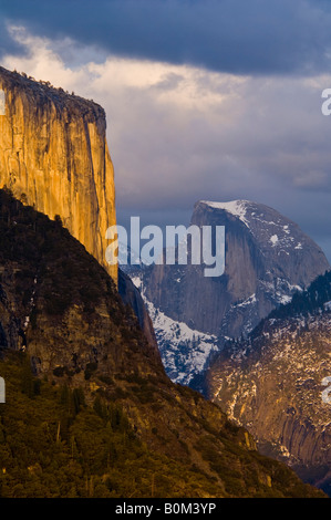 Sunset light on El Capitan and storm clouds over Half Dome and Yosemite Valley Yosemite National Park California - Stock Photo
