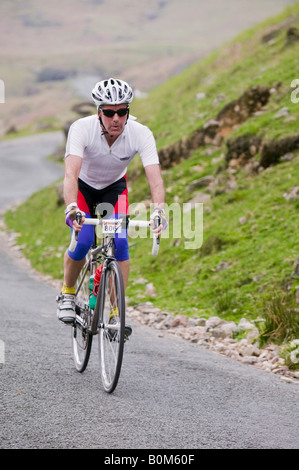 A cyclist descending Wrynose Pass on the Fred Whitton challenge in the Lake District - Stock Photo