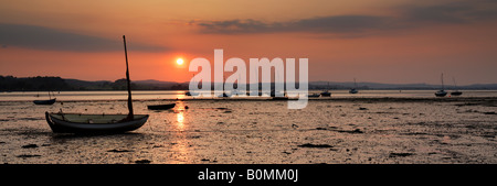 Sunset view of boats on the Exe Estuary at low tide, Lympstone, near Exeter, Devon, UK - Stock Photo