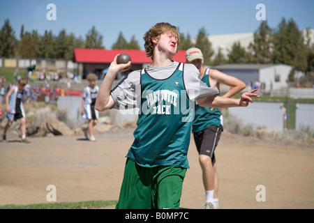 A middle school junior high school district track meet in the spring track season This is a boy s shotput - Stock Photo