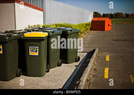 Paper recycling wheelie bins beside corrugated iron fence with larger recycling skip in distance New Zealand - Stock Photo