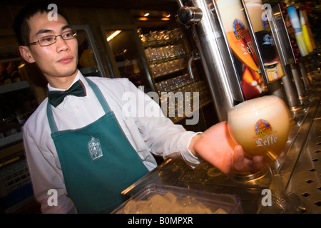 Chinese barman serves a Belgian Leffe beer in Le Roy d'Espagne bar. Grand Place, Bruxelles. Belgium - Stock Photo