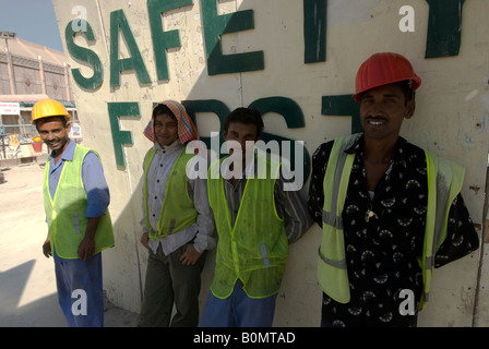 Four migrant workers take a break in the shade against a wall where is written: Safety first, Dubai. - Stock Photo