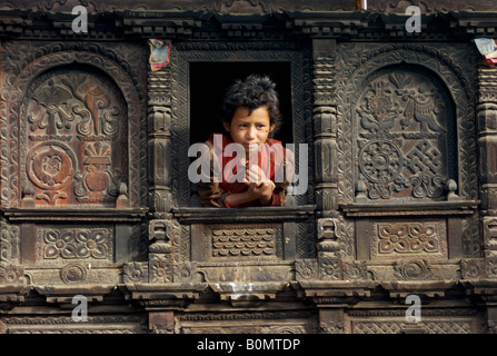 A girl leans out the window of her beautifully carved house, Gatlang, Tamang Heritage Trail, Nepal - Stock Photo