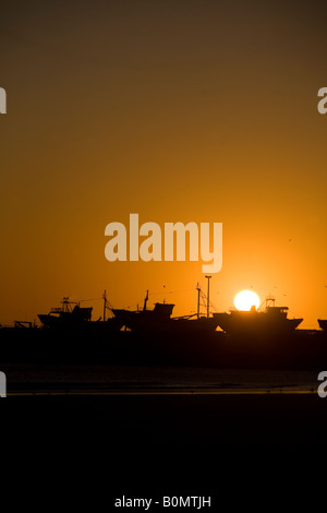 Fishing boats in harbour yard at sunset. Essaouira, Morocco - Stock Photo