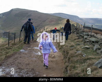 Young girl and her family walking the footpath over Mam Tor. Peak District National Park. UK - Stock Photo