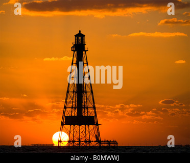 A brilliant fiery orange sky sunset over the ocean behind silhouette of Alligator Reef Lighthouse off Islamorada - Stock Photo
