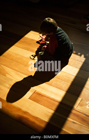 Boy aged six plays with toy plastic helicopter on floor of his room with full sun streaming through the window - Stock Photo