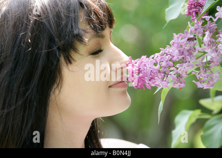 Woman smelling lilac branches - Stock Photo